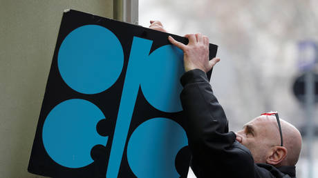 A man fixes a sign with OPEC's logo next to its headquarter's entrance in Vienna, Austria, November 29, 2017. © Reuters / Heinz-Peter Bader