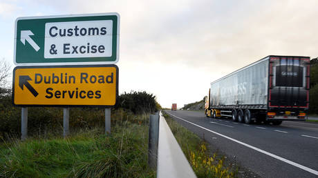 FILE PHOTO: A semi-truck passes a sign for Customs and Excise on a road near the border with Ireland near Kileen, Northern Ireland.