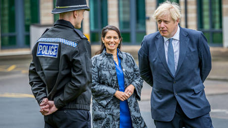 British PM Boris Johnson and Home Secretary Priti Patel speak with a police officer in Northallerton, Britain, July 30, 2020. © Reuters / Charlotte Graham / Pool