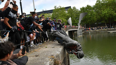 FILE PHOTO: Protesters throw statue of Edward Colston into Bristol harbour during a Black Lives Matter protest rally