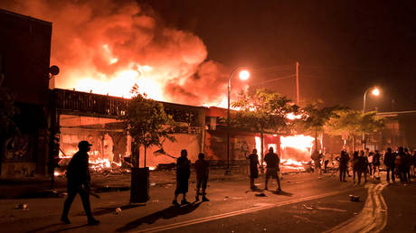 Flames rise from a liquor store and shops near the Third Police Precinct on May 28, 2020 in Minneapolis, Minnesota, during a protest over the death of George Floyd.