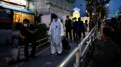 A government official sanitizes a street amid the coronavirus disease pandemic in Seoul, South Korea, September 17, 2020. © Reuters / Kim Hong-ji