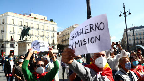 """People hold placards during a protest against government as Spanish PM Pedro Sanchez meets Madrid regional leader Isabel Diaz Ayuso, at Puerta del Sol square in Madrid, Spain, September 21, 2020. Placards read """"Government resignation"""". © Reuters / Sergio Perez"""