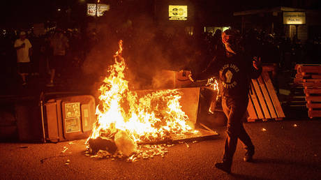A protester passes a dumpster fire on Saturday, Sept. 5, 2020, during a demonstration in Portland, Ore.