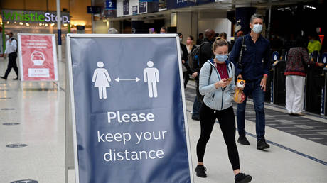 FILE PHOTO: People wearing masks pass a social distancing sign at Waterloo station in London. September 7, 2020. Toby Melville / Reuters