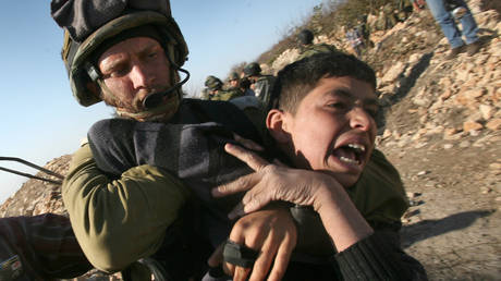 An Israeli soldier detains a Palestinian youth during a protest.