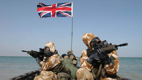 FILE PHOTO: Royal Marines of 539 Assault Squadron in full battle kit pictured beside a Union Jack flag days before the beginning of the Iraq war 2003.