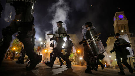 Police officers move past the Louisville City Hall to clear protesters from a plaza ahead of a 9pm curfew amid chaotic demonstrations in Louisville, Kentucky, September 23, 2020.