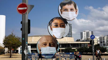 A sculpture decorated with images of people wearing masks in Tel Aviv, Israel. September 24, 2020. © Reuters / Nir Elias