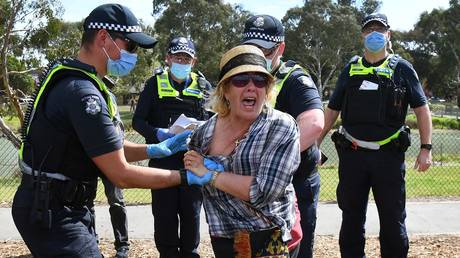 Victoria police arresting a protester in Melbourne suburbs © AFP / William West