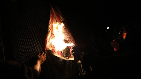 An American Flag is burned as protesters gather in front of the Mark O. Hatfield federal courthouse in downtown Portland as the city experiences another night of unrest on July 25, 2020 in Portland, Oregon