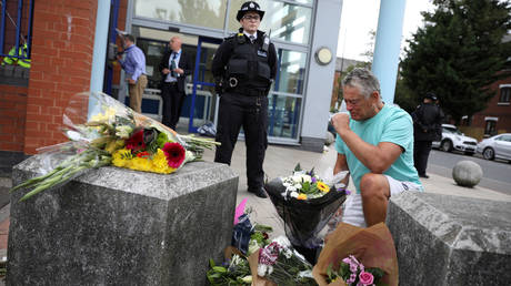 A man reacts as flowers are laid down outside the custody centre where a British police officer has been shot dead in Croydon, south London, Britain, September 25, 2020 © REUTERS/Tom Nicholson