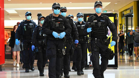 Victoria Police officers patrol through a shopping center following an anti-lockdown protest