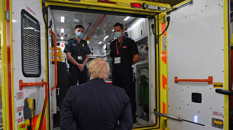 Britain's Prime Minister Boris Johnson talks with a paramedic