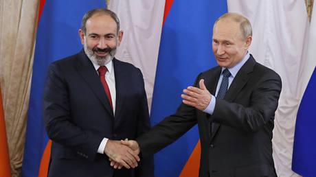 FILE PHOTO. Russian President Vladimir Putin shakes hands with Armenian Prime Minister Nikol Pashinyan. ©Yuri Kochetkov / Pool via REUTERS