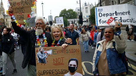 FILE PHOTO: Protesters hold placards during a demonstration against the lockdown and use of face masks, amid the coronavirus disease (COVID-19) outbreak, at Whitehall in London, Britain, August 29, 2020.
