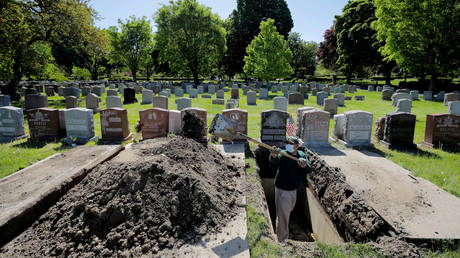 FILE PHOTO: A man prepares a grave for burial at Woodlawn Cemetery during the coronavirus disease (COVID-19) outbreak in Everett, Massachusetts.