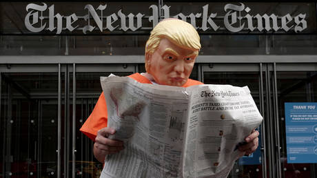 Mike Hisey dressed as Donald Trump in a prison jumpsuit reads the New York Times in front of the New York Times office