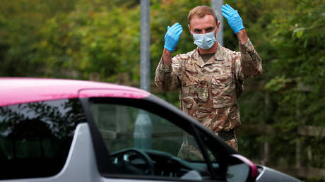 A UK soldier directs cars at a Covid-19 testing center in Blackburn. © REUTERS/Phil Noble