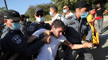 Policemen detain a man during a demonstration against the Israeli government before parliament passed legislation restricting protests amid a nationwide lockdown, outside the Knesset in Jerusalem, September 29, 2020.