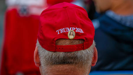 A man has a Jesus Christ pin affixed to a Trump 2020 hat during a Make American Great Again rally with Eric Trump