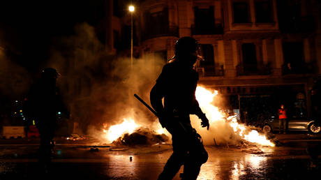 Police officers stand in front of burning garbage containers as Catalan pro-independence activist protest in Barcelona, Spain, on October 1, 2020. © Albert Gea / Reuters.