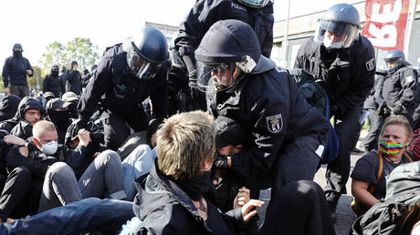 A police officer detains a counter-protester demonstrating against the far-right party The Third Way in Berlin, Germany on October 3, 2020.