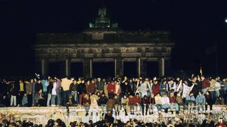 People from East and West Berlin climb on the Wall at the Brandenburg Gate on 9th November 1989, Berlin, Germany