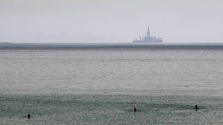 An off-shore oil and gas exploration drillship is seen in the background as people bathe in the Mediterranean on May 19, 2020,