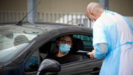 FILE PHOTO: A doctor checks the identity of a man before taking swabs. Toulouse. France. April 28th 2020