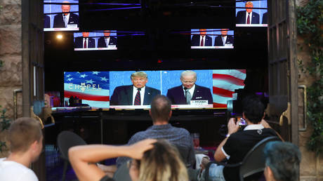 FILE PHOTO: People sit and watch a broadcast of the first debate between President Donald Trump and Democratic presidential nominee Joe Biden at The Abbey, with socially distanced outdoor seating, on September 29, 2020 in West Hollywood, California