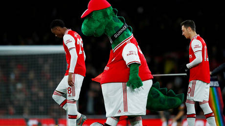 Mesut Ozil (R) has offered to help Arsenal mascot Gunnersaurus, who is said to be facing the sack. © Reuters