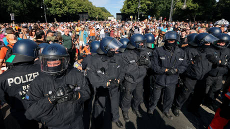 Police officers stand next to demonstrators blocking the street during a protest near the Brandenburg Gate against the government's restrictions amid the coronavirus disease outbreak, in Berlin, Germany, August 1, 2020. © Reuters / Fabrizio Bensch