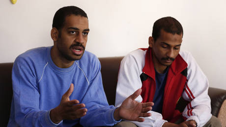 March 30, 2019, file photo. Alexanda Amon Kotey, left, and El Shafee Elsheikh speak during an interview with The Associated Press at a security center in Kobani, Syria.  © AP Photo/Hussein Malla