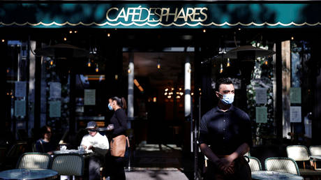 FILE PHOTO: A waiter wearing a mask stands in front of a café in Paris. June 2020. © Reuters/Christian Hartman