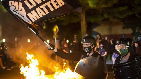 FILE PHOTO: Protesters gather in front of a fire near the North police precinct during a protest against racial injustice and police brutality on September 6, 2020 in Portland, Oregon
