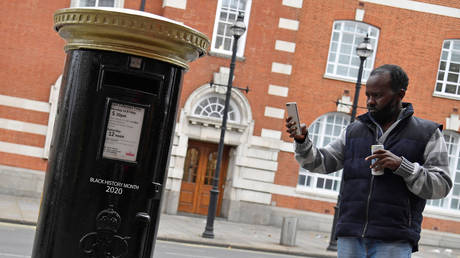 A pedestrian films a Royal Mail postbox, painted black instead of traditional red, to honour Black Britons, as part of the forthcoming Black History Month, in Brixton, London, Britain, September 30, 2020.