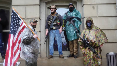 FILE PHOTO: Armed demonstrators attend a rally in front of the Michigan state capital building to protest the governor's stay-at-home order on May 14, 2020 in Lansing, Michigan
