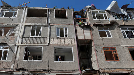 An elderly woman stands on the balcony of an apartment building damaged during the military conflict over the breakaway region of Nagorno-Karabakh, in Stepanakert October 11, 2020.