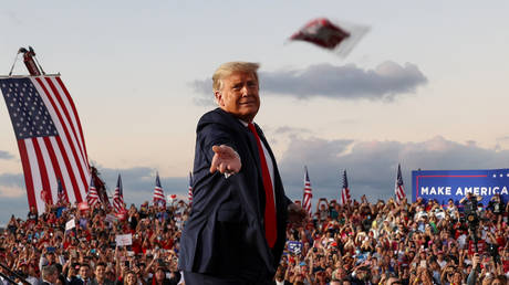 President Donald Trump tosses face masks to the crowd as he takes the stage for a campaign rally at Orlando Sanford International Airport in Sanford, Florida, October 12, 2020.