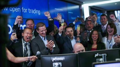 FILE PHOTO: Les employés réagissent alors que Jay Heller, responsable des marchés financiers et de l'exécution de l'offre publique initiale (IPO) de Nasdaq Inc, centre, ouvre la négociation sur Zoom Video Communications Inc. lors de l'introduction en bourse de la société au Nasdaq MarketSite le 18 avril 2019 dans New York City