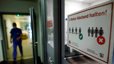 "FILE PHOTO: A hospital worker walks past a sign reading ""Keep two meters distance"" on a door to an intensive care unit in Eschweiler, Germany."