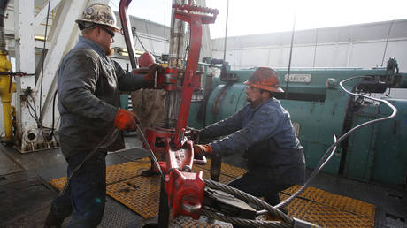Roughnecks wrestle pipe on a True Company oil drilling rig outside Watford, North Dakota