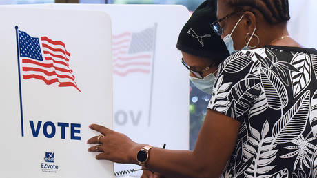 Women wearing face masks fill out vote-by-mail ballots at the Orange County Supervisor of Elections office on October 15, 2020 in Orlando, Florida