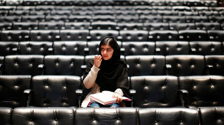 """FILE PHOTO: Malala Yousafzai signs a copy of her book before an event launching her memoir, """"I Am Malala"""", at the Southbank Centre in central London, Britain, October 20, 2013"""