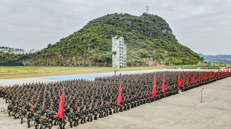 More than 1,000 officers and soldiers sit and listen during a new recruit mobilization conference in Nanning, Guangxi province, China, Oct. 10, 2020