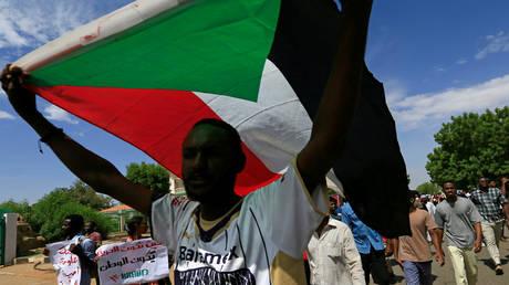 FILE PHOTO: A demonstrator is waving the flag of Sudan  in Khartoum, Sudan, on August 17, 2020.