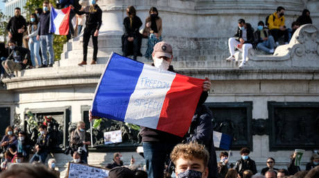 A protester holding a French flag with 'Freedom of Speech' written on it during the tribute.