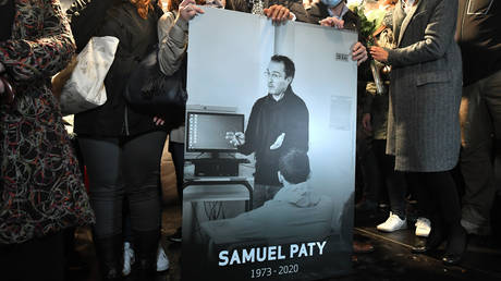 Relatives and colleagues hold a photo of Samuel Paty during a rally on October 20, 2020
