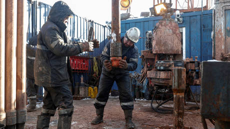 Drilling crew members move a pipe while working at an oil rig in the Yarakta Oil Field in Irkutsk Region, Russia